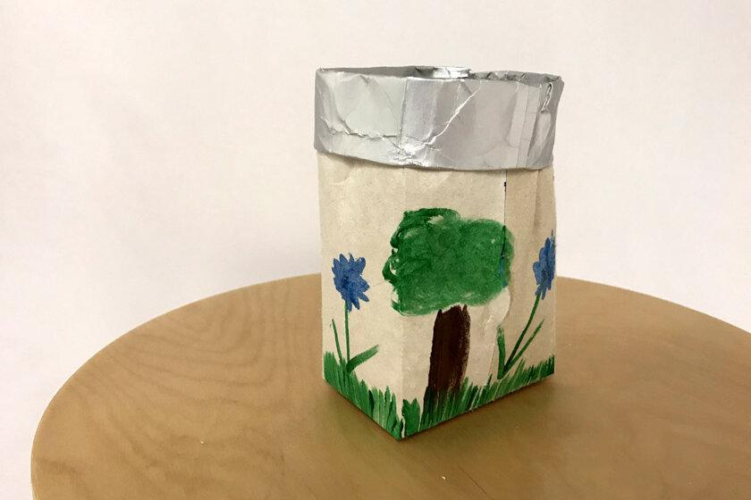 Milchkarton umgewandelt in einem Blumentopf verziert mit einer grünen Landschaft und blauen Blumen mit einen roßen Baum in der Mitte.