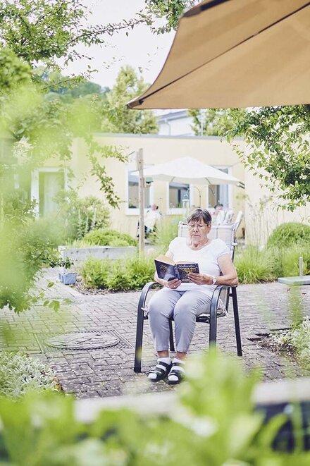 Eine Bewohnerin liest im Garten ein Buch