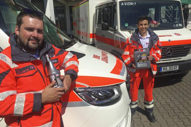 Zwei Rettungskräfte halten gespendete Motoröle und Autopflegemittel des Unternehmens Liqui Moly in der Hand.