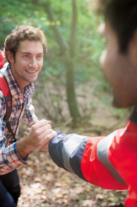 Ein Mann in Johanniter-Kleidung reicht einem anderen Menschen helfend die Hand.