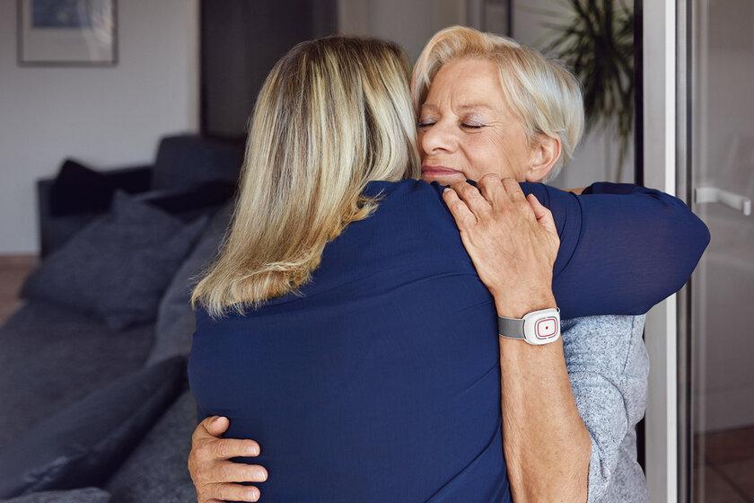 Eine jüngere und eine ältere Frau umarmen sich an einer offenen Terrassentür..