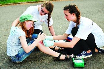 Zwei Schulsanitäterinnen versorgen ein Mädchen, das hingefallen ist.