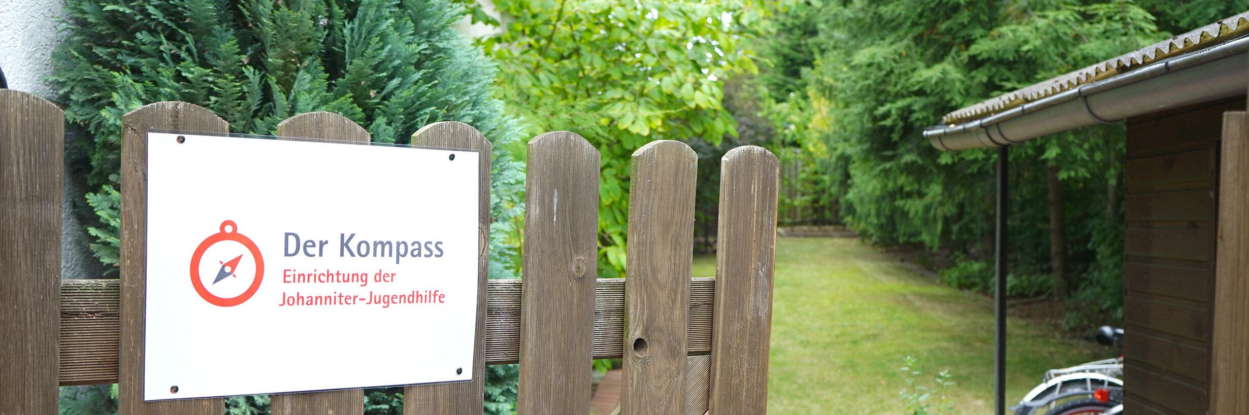 """geöffnetes Gartentor mit Schild """"Johanniter-Jugendhilfe Kompass"""""""