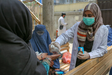 A women is handing over a bottle of desinfectant to another woman