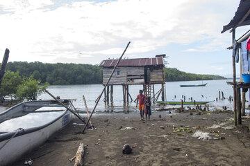 Ein Boot, ein Haus und zwei Kinder auf matschigem Untergrund, im Hintergrund Wasser