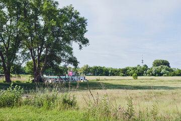 Ein weiter Blick aus der Einrichtung Johanniter Seniorenanlage Heinrich-Gau auf Felder und ein Schiff auf dem Fluss