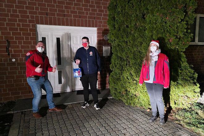 Johanniter-Ehrenamtliche Philip und Tina bringen ihren Kolleginnen und Kollegen kleine Wichtel-Geschenke an die Haustür und überreichen diese mit Abstand.