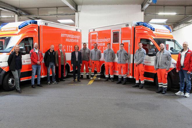 Mitarbeitende, Vorstände, Pfarrer und Gäste vor den beiden neuen Rettungswagen.