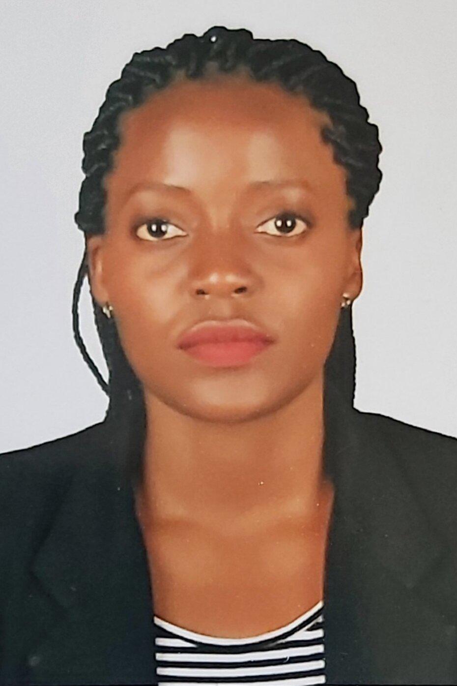 Ein Porträt von Jane Nakanwagi. Sie ist eine schwarze Frau, trägt lange Braids, ein weiß-schwarz gestreiftes Shirt und einen schwarzen Blazer