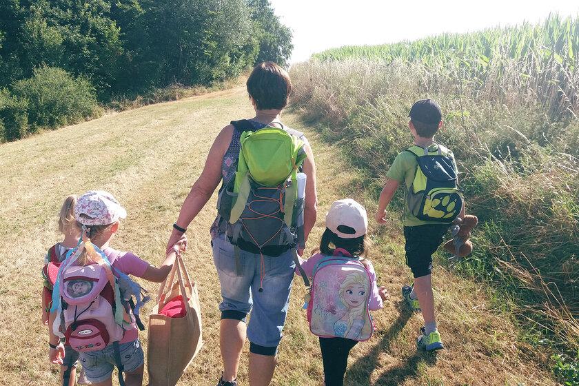 Vier Kinder und eine Frau gehen mit kleinen Rucksäcken am Rand eines Feld vorbei.