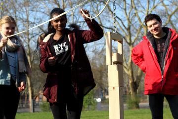 Zwie Jugendliche halten ein Seil mit dem Sie einen Turm aus Holzklötzen errichten. Ein junger Erwachsener in Johanniter-Jugend-Jacke steht im Hintergrund.