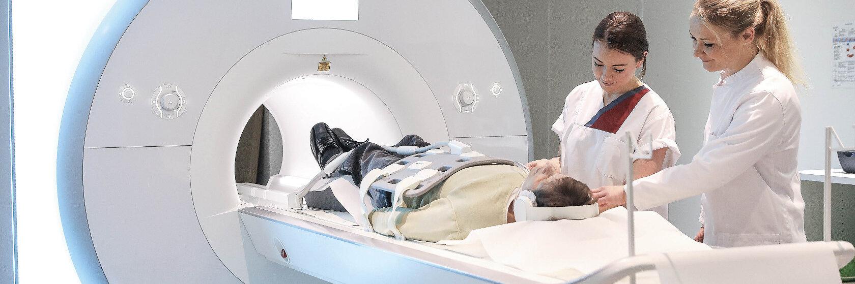 Mitarbeiterinnen der Johanniter GmbH führen eine Kernspintomographie durch.