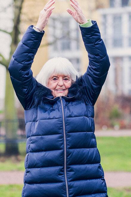 Eine Damen in einer blauen Jacke macht Sport in einer Gruppe