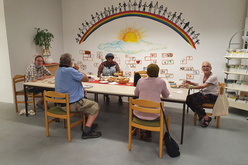 5 Personen sitzen um einen Tisch und essen