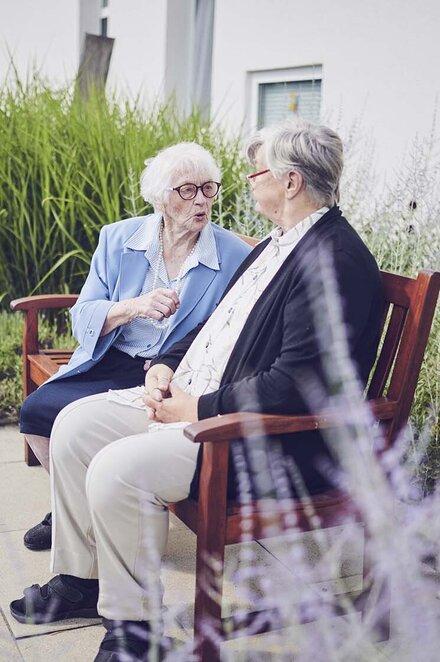 Zwei Bewohner genießen die frische Luft und sitzen auf einer Bank