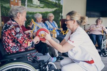 Eine Gruppe von Senioren beim Aktivierungsangebot mit Seil und Ring