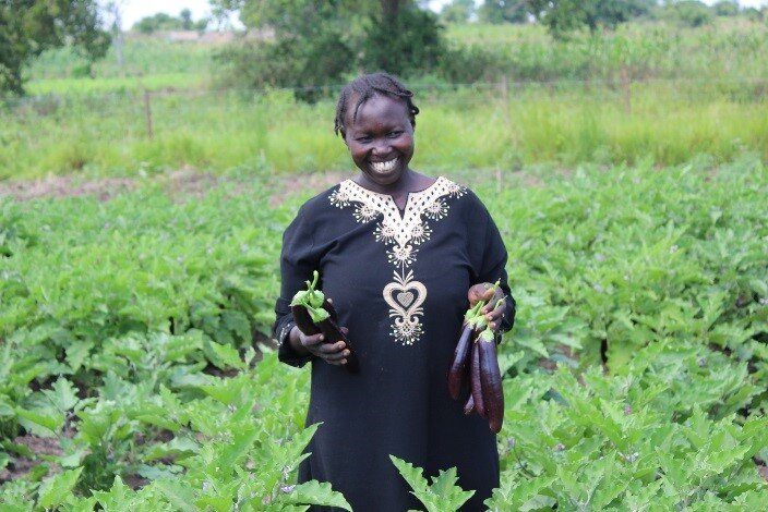 A smiling woman stands on her field with eggplants in her hand