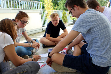 Eine Gruppe Jugendliche sitzt im Kreis und unterhält sich über Mitschriften