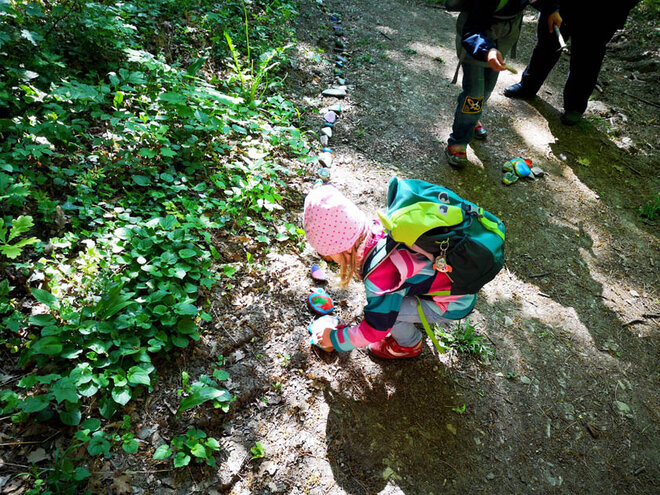 Kita-Kinder legen die farbenfroh bemalten Steine in den Sultmer Walt an das Ende der meterlangen Steinschlage.