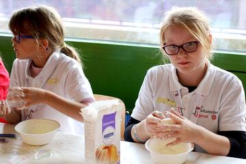 Zwei Mädchen stellen eine Knetmasse mit Kartoffelstärke her.