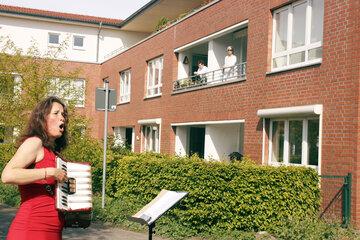 Eine Frau im roten Kleid singt und spielt dazu Akkordeon, auf Balkons hören Menschen zu.