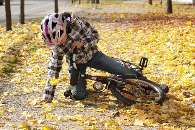 Kind stürzt mit Fahrrad auf rutschigem Herbstlaub