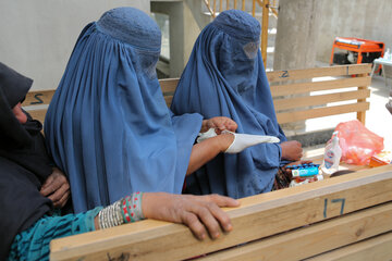 Two women recieve gloves and disinfection material for women in Kabul