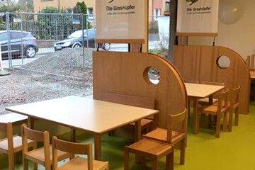 Kleine Stühle und Tische in Holzoptik, auf denen die Kinder und Erzieherinnen und Erzieher bei den Mahlzeiten sitzen können.