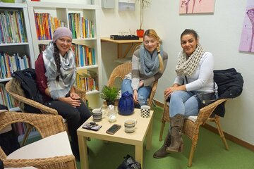 Drei Mütter sitzen mit einem Kaffee an einem kleinen runden Tisch in der Kita.