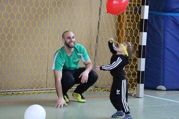 Ein Vater schaut zu, wie sein kleiner Sohn vor einem Fußballtor einen Ballon hochwirft.