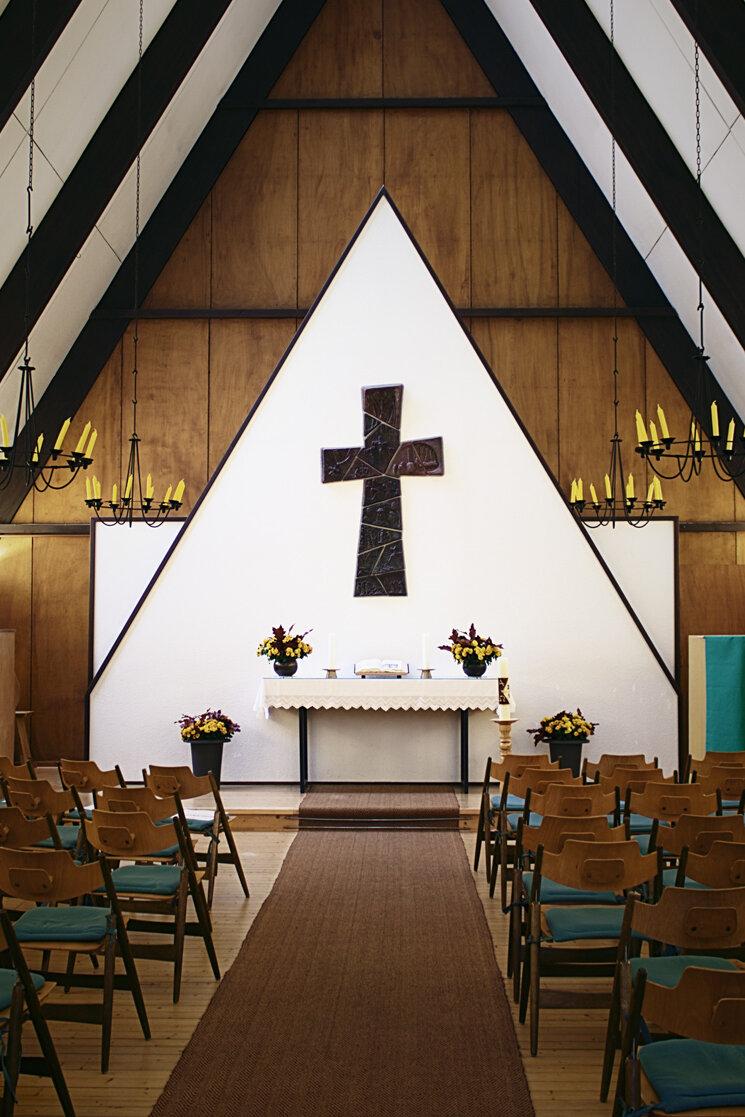Die Holzkirche liegt auf dem parkähnlichen Geländes des Hospiz