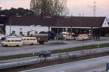 Rettungsfahrzeuge der Johanniter vor einem Gebäude direkt neben der Autobahn.