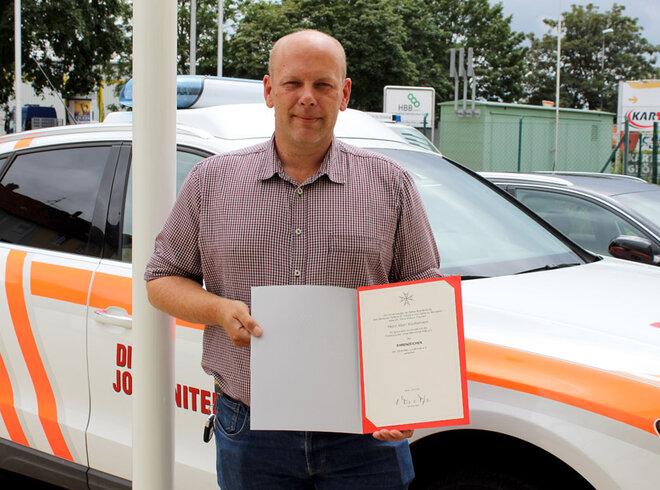 Marc Küchemann steht vor einem Johanniter-Fahrzeug und zeigt sein Ehrenzeichen
