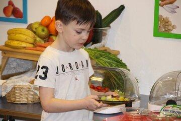 Ein Junge nimmt sich an einem Büfett Weintrauben und Käse.
