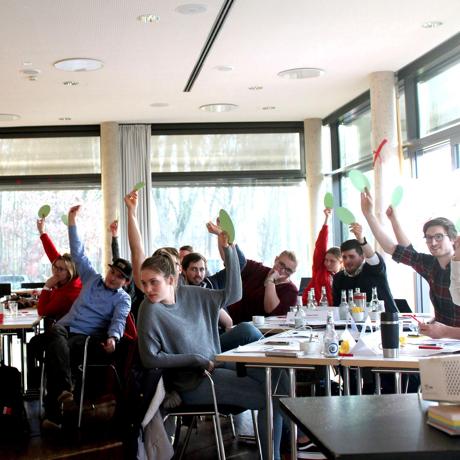 Mehrere junge Menschen sitzen an Tischen zusammen, schauen in die Kamera und halte Abstimmungskarten hoch.