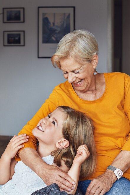Eine ältere Frau lächelt ihrer Enkelin zu