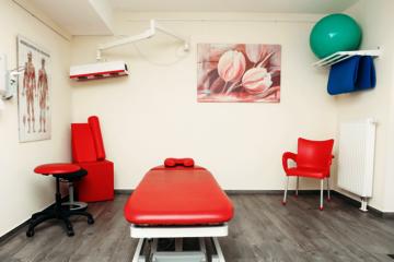 Physiotherapeutische Behandlungsraum mit roter Liege im Johanniter-Stift Köln-Flittard