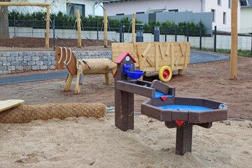 Spielpferd aus Holz und Wasserspielanlage der Kita am Wieter.