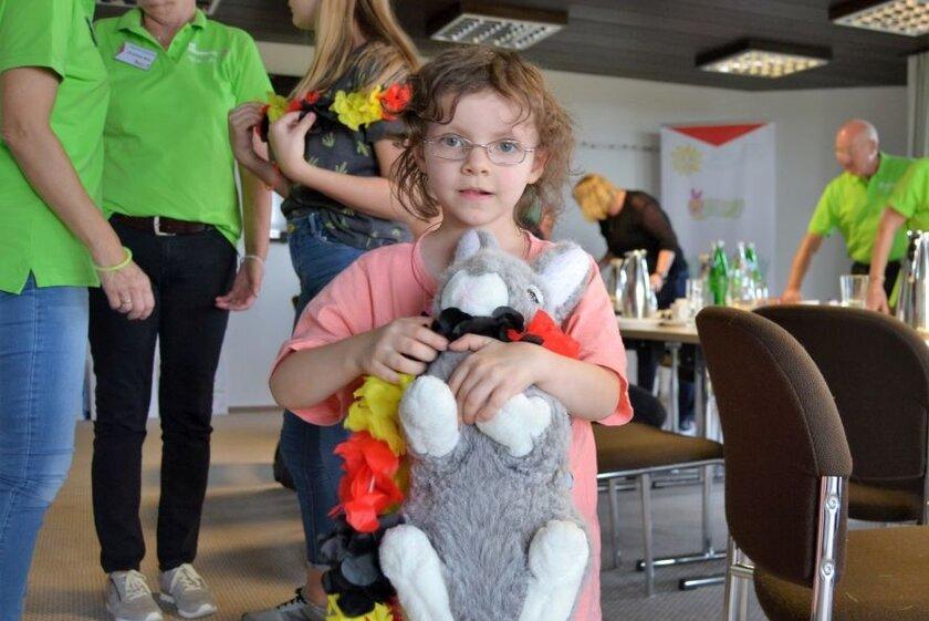 Ein Kind, das vom Hospizdienst begleitet wird, hält bei einem Treffen einen Teddy im Arm.