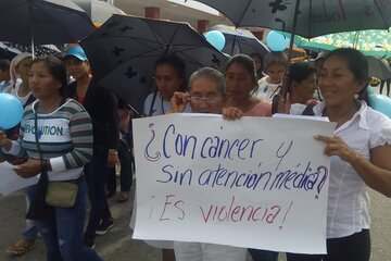 """Eine Demonstration, auf dem Plakat steht """"Krebs und keine medizinische Behandlung? Das ist Gewalt!"""""""