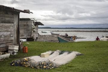 Ein Fischernetz liegt neben einem Haus, im Hintergrund ist Wasser zu sehen