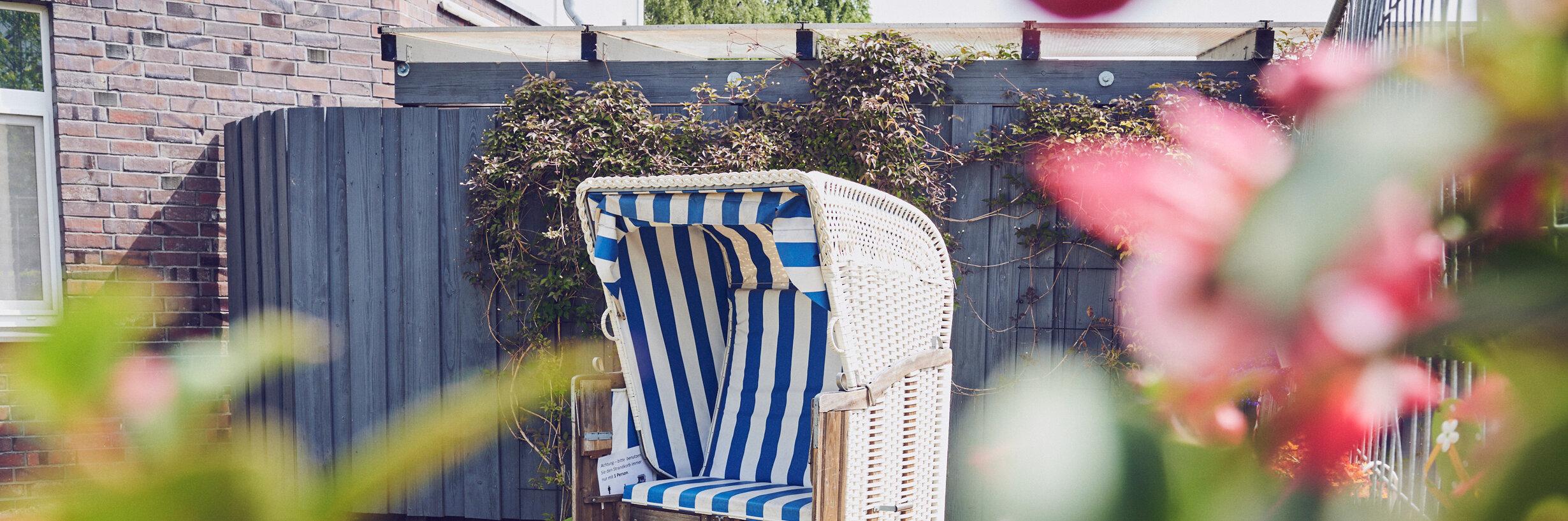 Blau-weißer Strandkorb in einer ruhigen Lage am Haus am Rosarium in Uetersen.