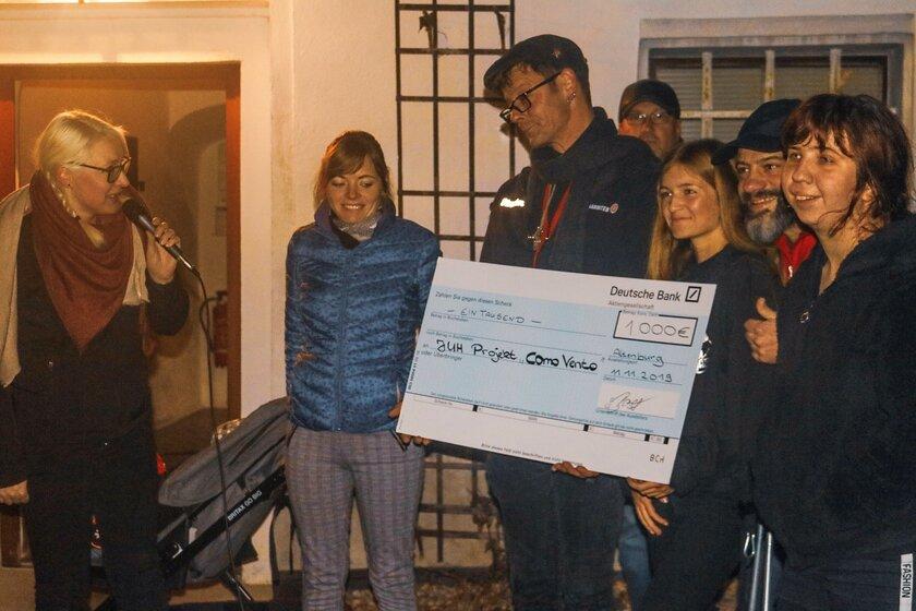 Janek Rochner-Günther, Leiter von Como Vento, nimmt Spendencheck der Deutschen Bank entgegen.