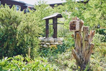 Im grünen Naturgarten sind Brunnen, ein vertrockneter Baumstamm sowie ein Insektenhaus im Johanniter-Haus Köln Porz zu sehen.