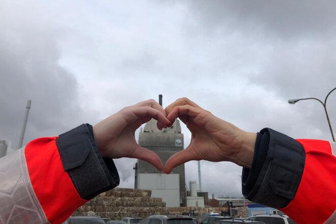 Zwei Hände bilden gemeinsam ein Herz vor dem Hintergrund eines Firmengeländes.