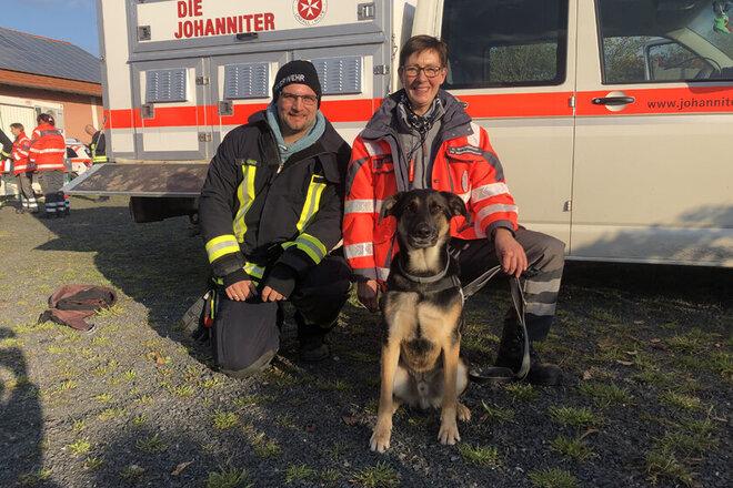 Rettungshund Poirot und Rettungshundeteam nach dem Einsatz. Im Hintergrund ist ein Einsatzfahrzeug der Johanniter-Rettungshundestaffel.