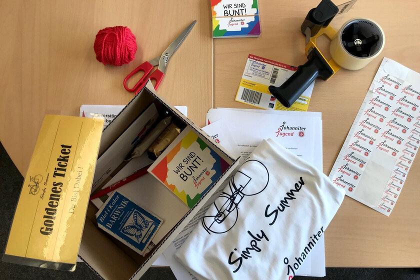 Ein Paket liegt ausgepackt auf einem Tisch. Darin sind unter anderem Aufkleber, ein T-Shirt mit Simply-Summer-Aufdruck, ein Faden, Süßigkeiten, Ein Kugelschreiber.