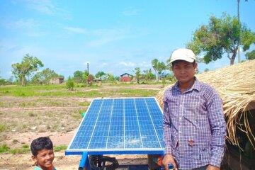Ein Mann und sein Sohn neben einer solarbetriebenen Wasserpumpe auf einem Feld.