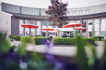 Rondell mit Sonnenschirme und Gartenmöbel vor dem Eingang der Johanniter Seniorenanlage Heinrich-Gau in Wedel