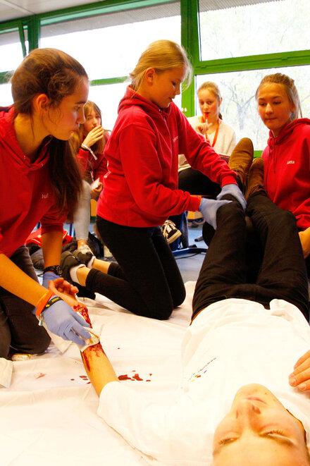 Drei Mädchen kümmern sich um einen verletzten Jungen, der am Boden liegt. Ein Mädchen hält die Beine hoch. Ein anderes Mädchen versorgt eine Wunde.